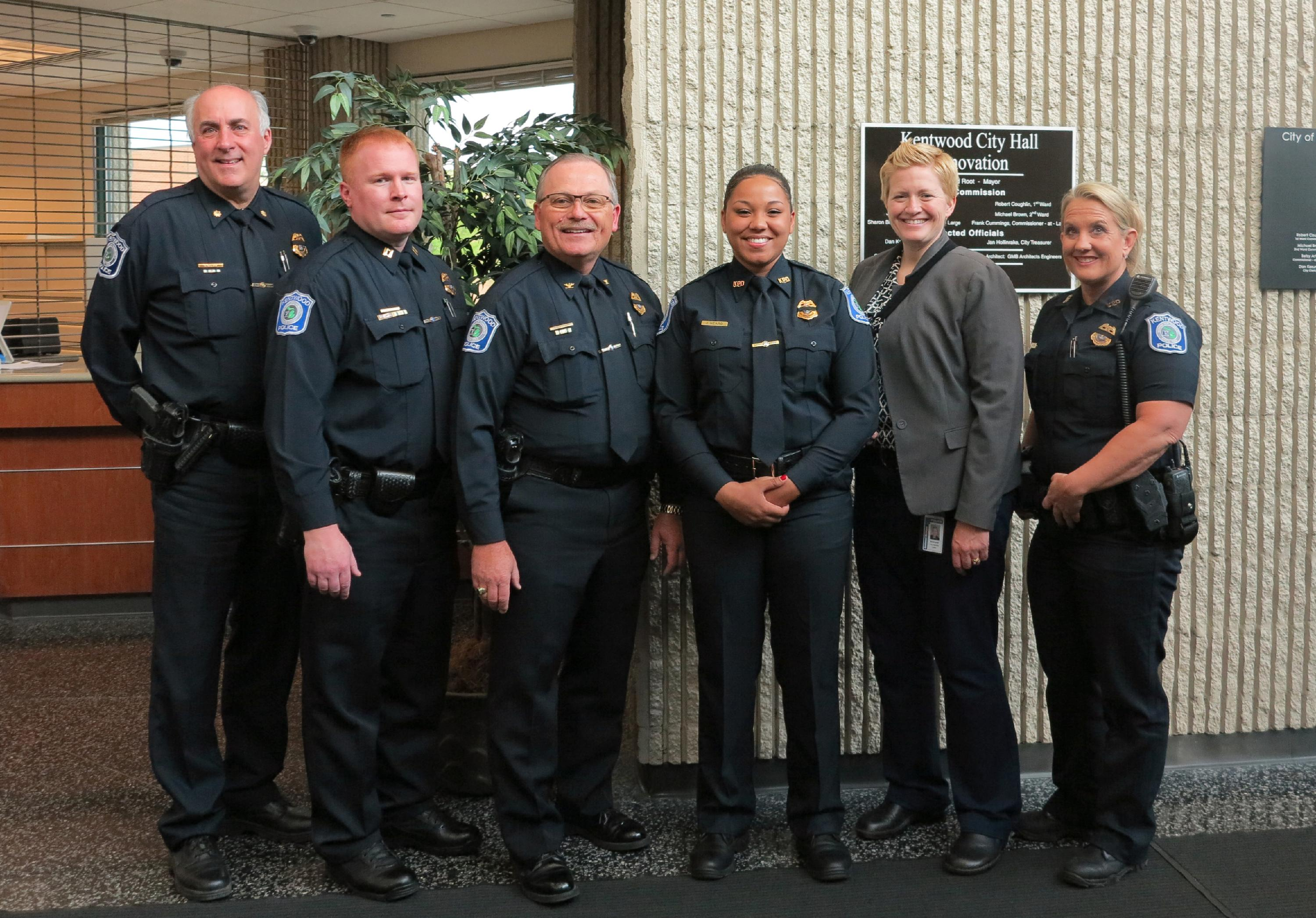 DC Roberts, Capt. Litwin, Chief Hillen, Officer Heard, Captain Morningstar and Officer Clark stand together and smile for a photo following Officer Heard's swearing in.