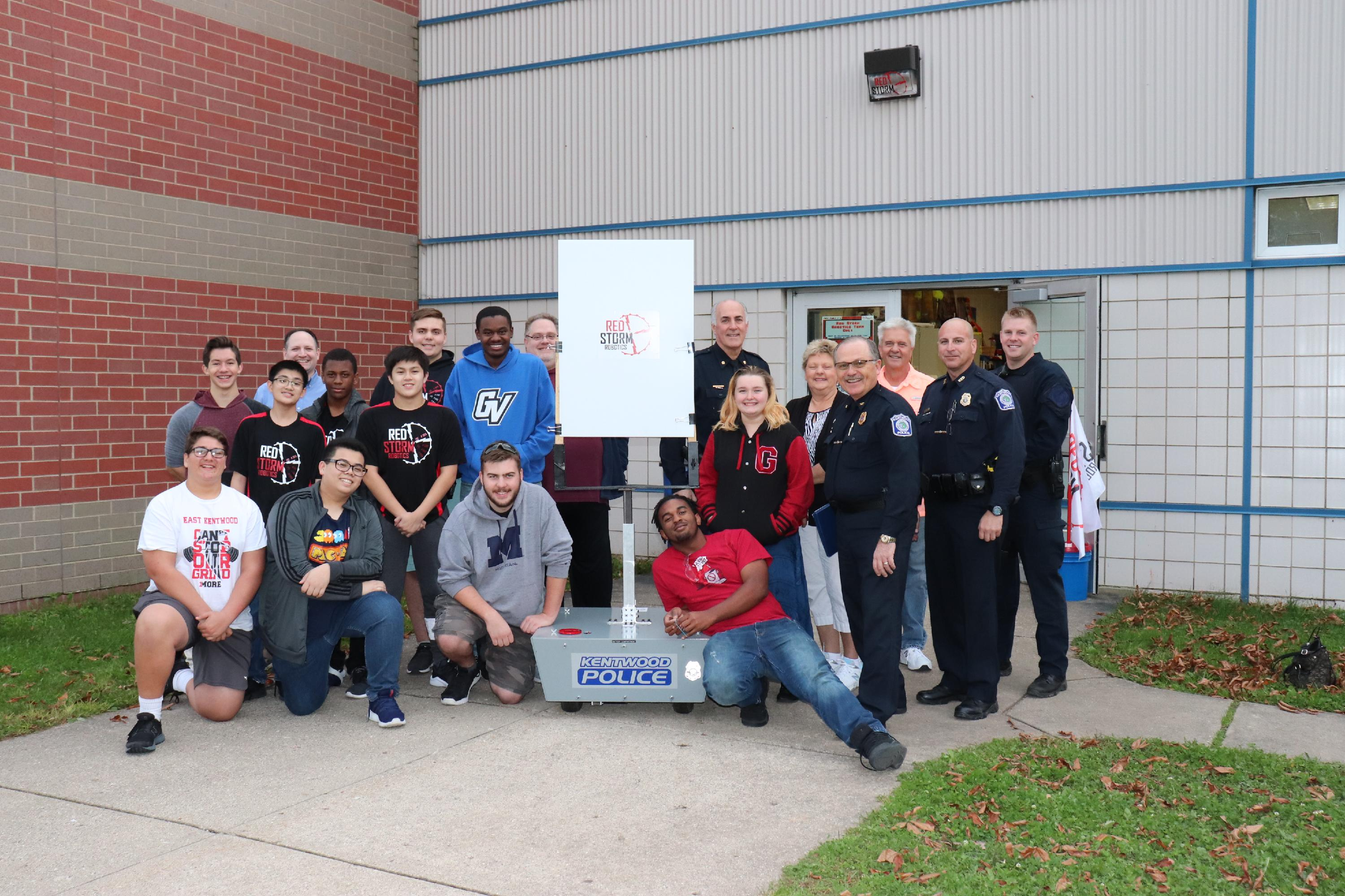Chief Hillen, Deputy Chief Roberts, Officer Willshire, special response team member Officer Vanderbent, Kentwood Public School students, robotics team mentors and representatives from Target Solutions USA smile for a picture with the Robotic Moving Target System.