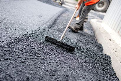 Man raking asphalt
