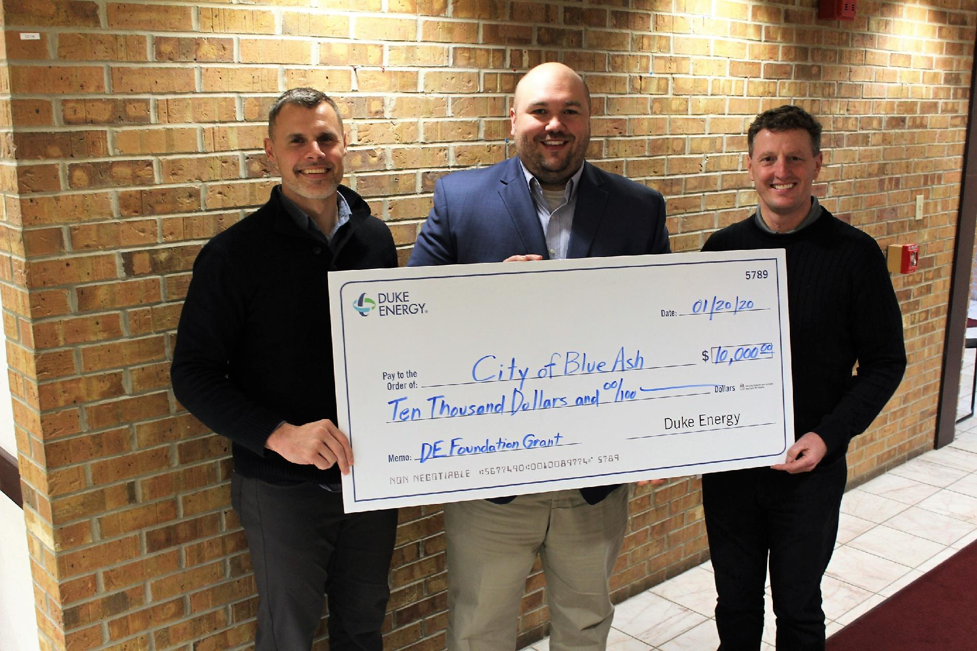 Blue Ash Parks and Recreation Director Brian Kruse, Duke Energy Sr. Government Affairs Specialist J. Chad Shaffer, and Blue Ash City Manager David Waltz hold large grant check